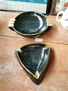 Two Guinness advertising ashtrays.