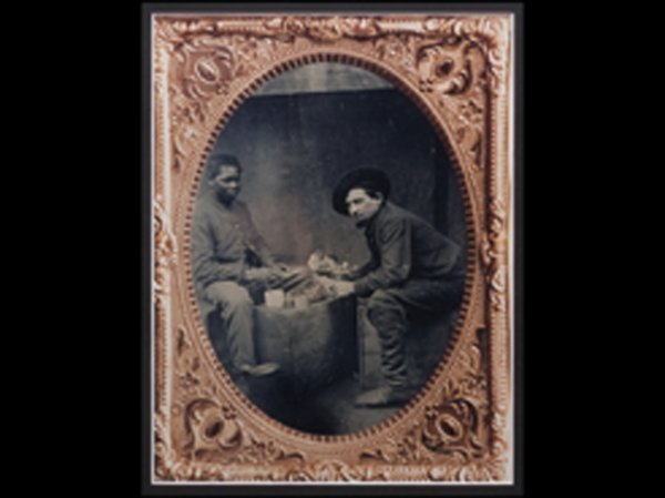 928: D23 - SEATED WHITE MAN AND BLACK MAN EATING ON CRA
