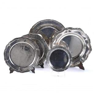 PERUVIAN PLATTER AND FOUR ROUND TRAYS IN SILVER, SECOND