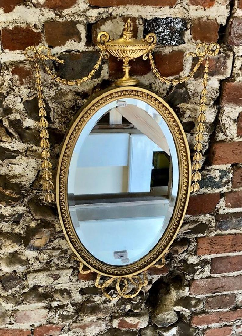 A Victorian gilwood and composite oval mirror