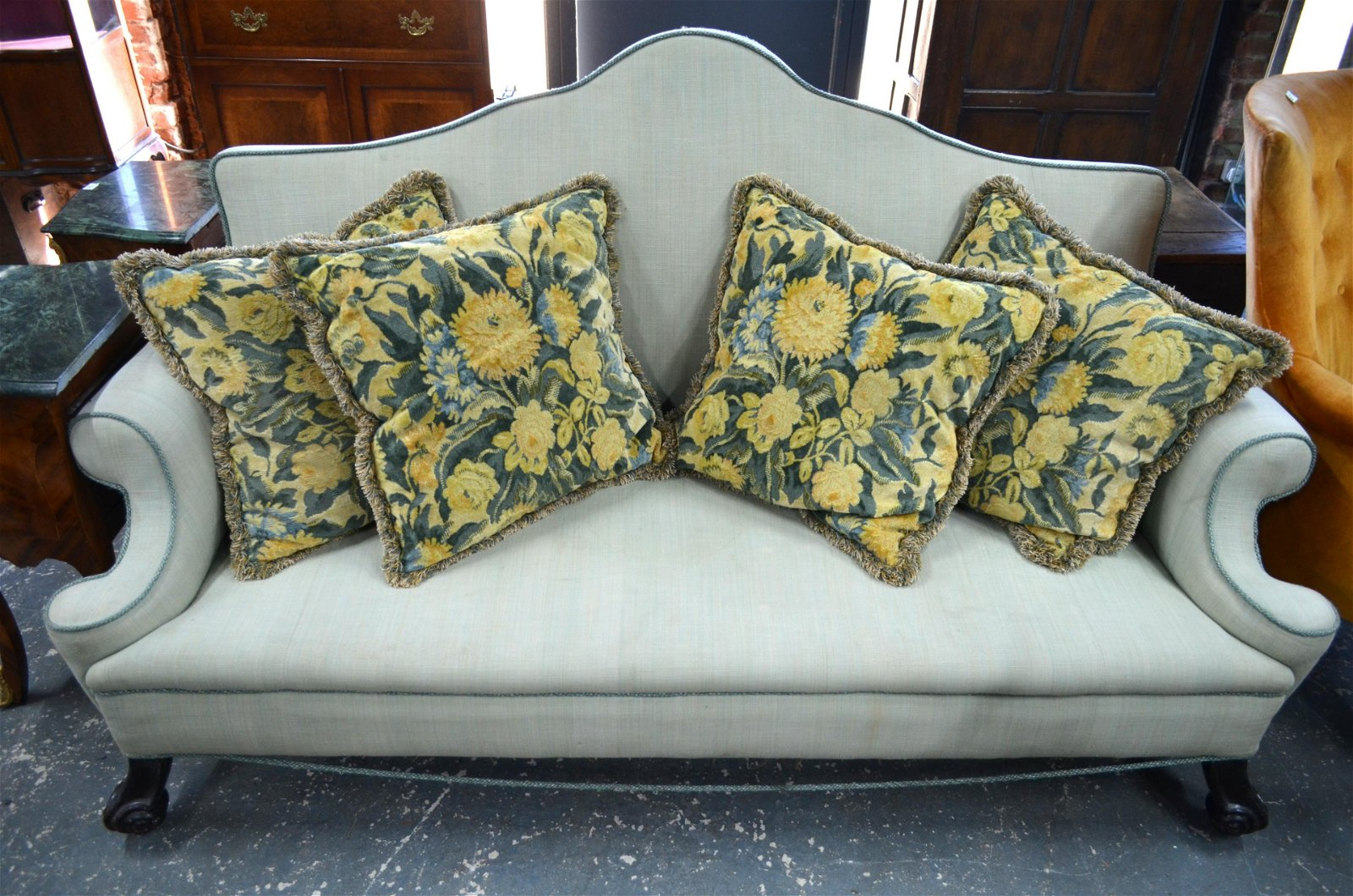 A Queen Anne style hump back sofa with scroll arms