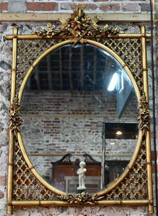 An antique giltwood framed mirror with oval plate