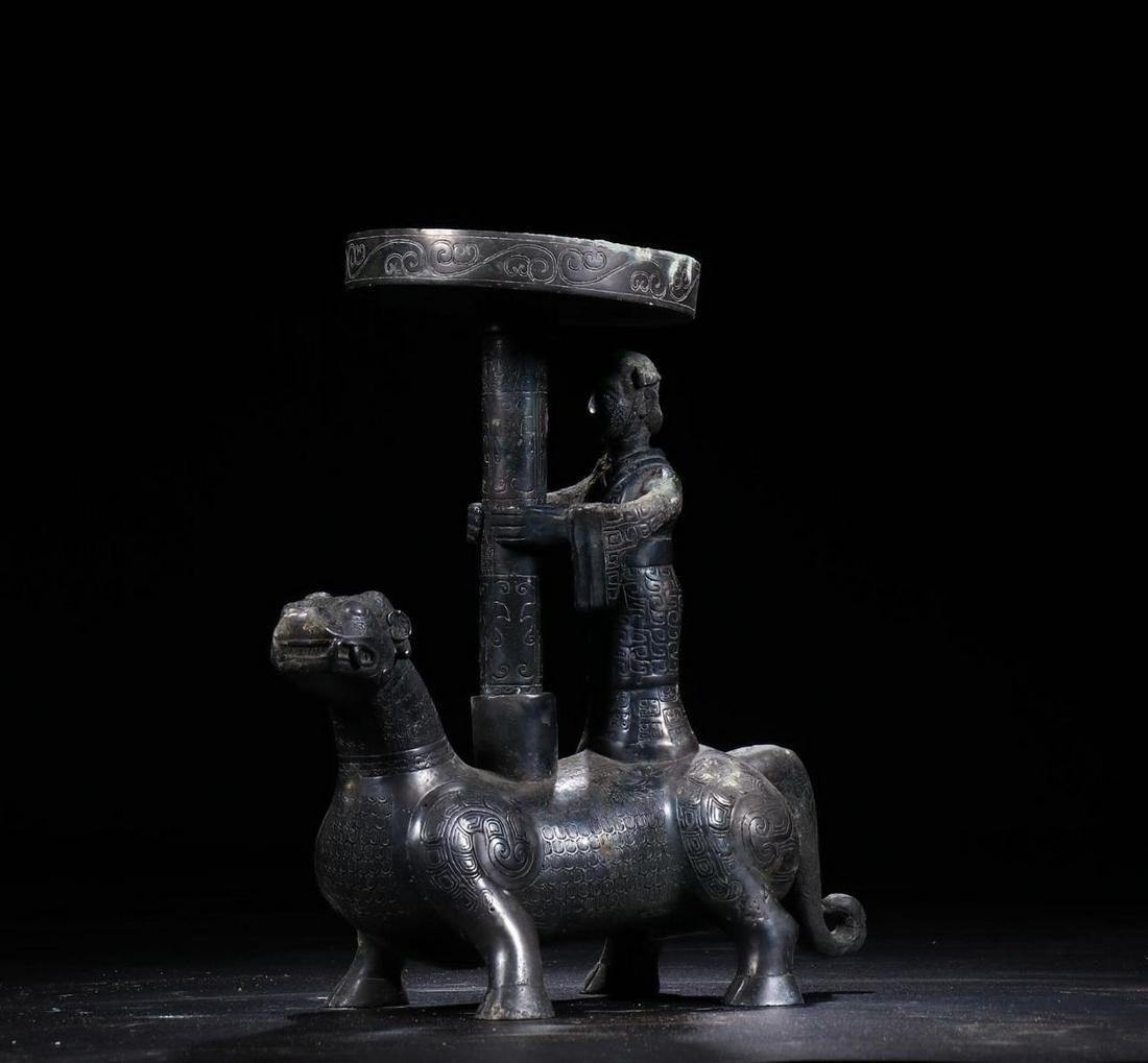 A CHINESE ARCHAIC BRONZE MYTHICAL BEAST SHAPED CANDLE