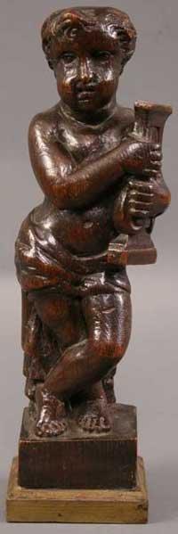 4: A 17th Century Carved Oak Figure of a Cherub holding