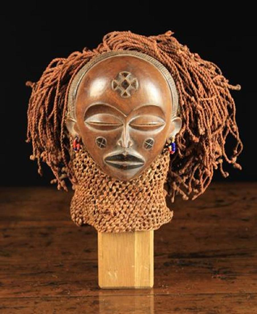 An African Chokwe Mwana Pwo Mask. The carved wooden