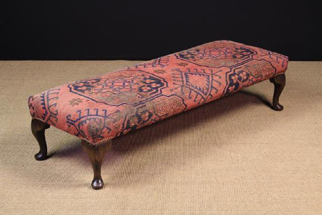 A Long Upholstered Vintage foot stool covered in carpet
