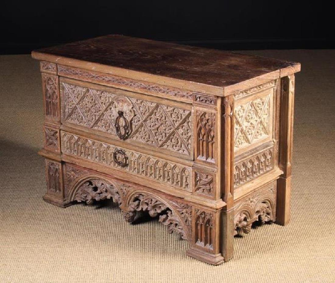 A Low 'Gothic' Oak Chest of Drawers richly carved in