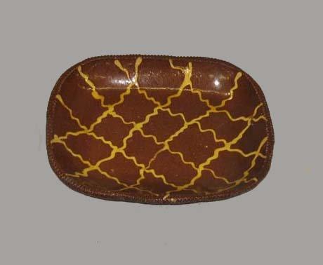 511: REDWARE LOAF PAN. Coggled rim with yellow slip dec