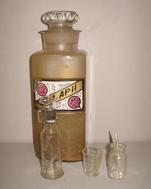 21: FOUR GLASS MEDICAL ITEMS. Pictured is an apothecary
