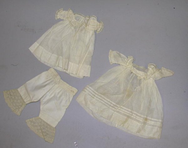 19: THREE PIECES DOLL CLOTHING. Shown are two antique w