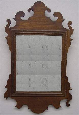 CHIPPENDALE SCROLL MIRROR. Mahogany with an old dar