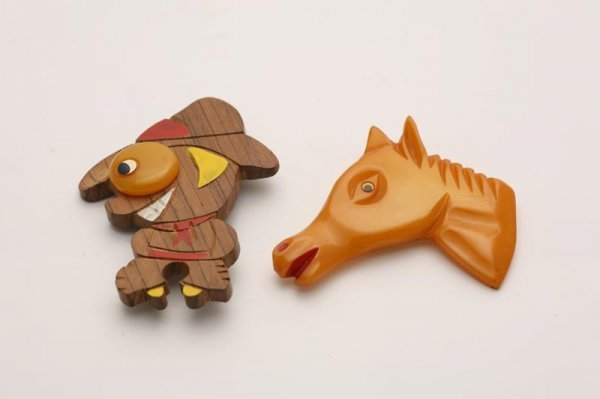 1008: TWO WESTERN THEME BAKELITE PINS. Carved buttersco
