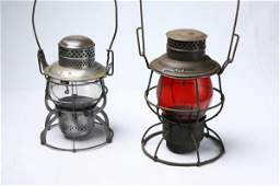 896: TWO RAILROAD LANTERNS. One has a red globe and the