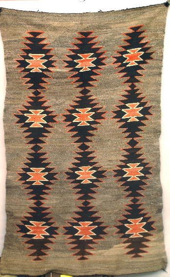 834: TRANSITIONAL NAVAJO RUG. A carded gray background