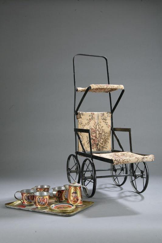 1007: DOLL STROLLER AND TEA SET. Metal stroller with fl