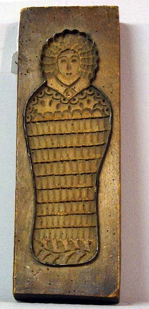 8: WOODEN COOKIE BOARD. Swaddled baby with a