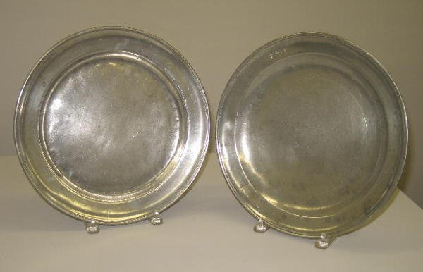 18: TWO PEWTER CHARGERS. One has stamped initials on th
