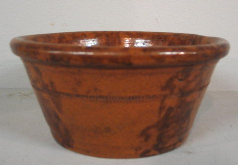 426: REDWARE BOWL. Tapered sides with a coggled, incise