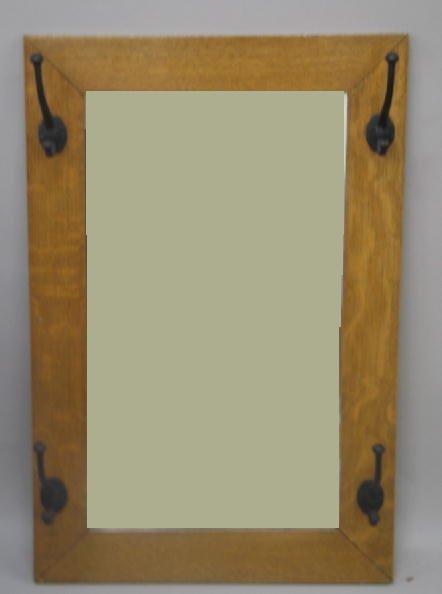 1015: MIRROR HAT RACK. Oak frame in a golden finish wit