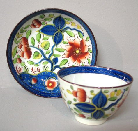 6: GAUDY DUTCH HANDLELESS CUP AND SAUCER. Sunflower in