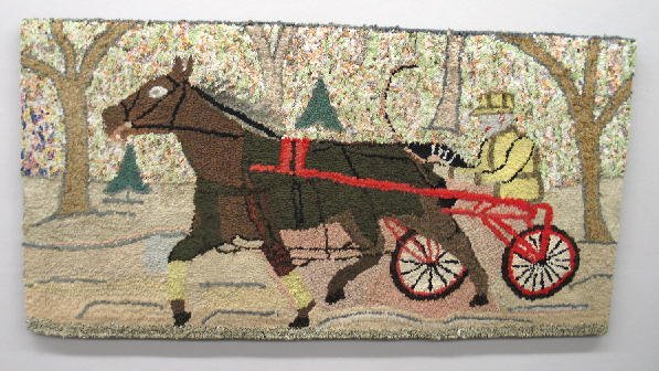 23: HOOKED RUG. Horse with rider in a sulky on tree lin