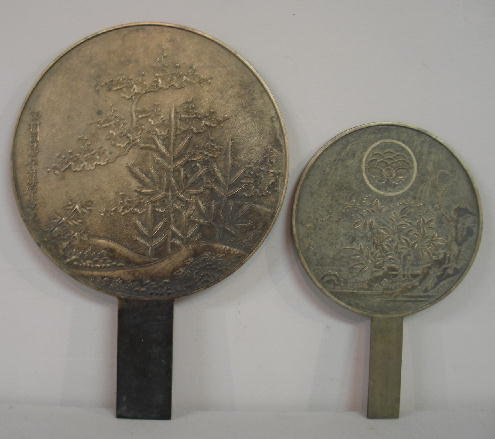 24: TWO ORIENTAL MIRRORS. Bronze or possibly paktong wi