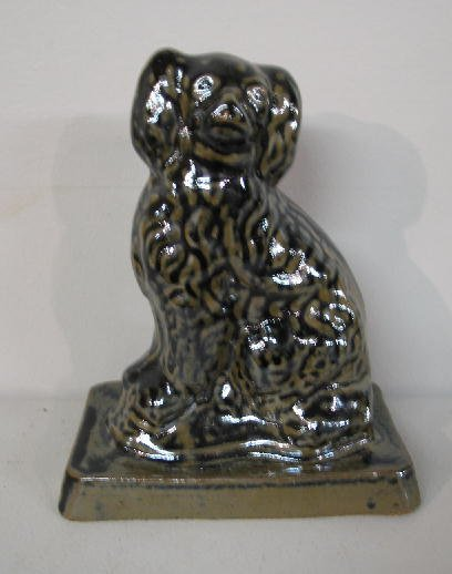 357: POTTERY DOG. White clay seated spaniel with unusua