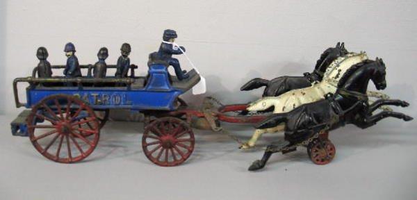 "367: CAST IRON ""PATROL"" WAGON TOY. Three horses pull a"