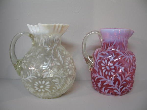 6: TWO GLASS PITCHERS. Clear and light cranberry with o