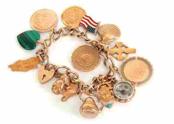 A 9CT GOLD CHARM BRACELET with thirteen 9ct gold c
