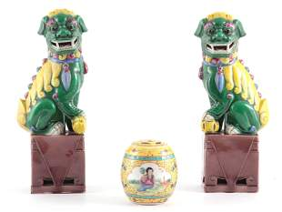A PAIR OF CHINESE SEATED FOO DOGS ON BROWN PEDESTAL