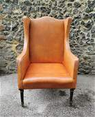 An early 20th century leather wing back armchair by