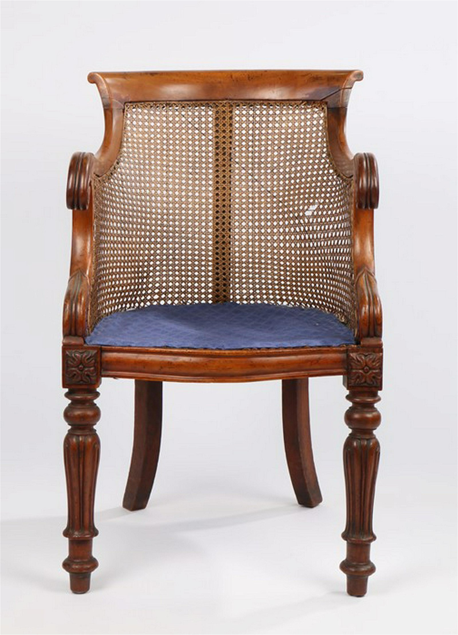 Regency mahogany bergere chair, the arched caned back
