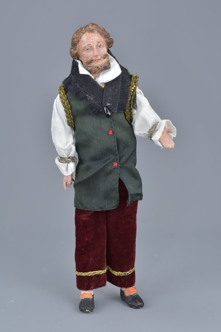 A vintage doll figure of a man in original clothing.