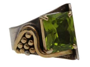 A SILVER AND GOLD PLATED RING WITH A GREEN STONE