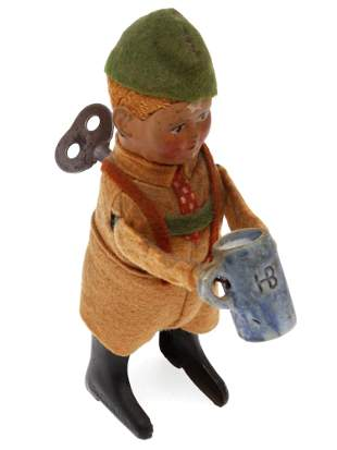 AN ANTIQUE GERMAN SCHUCO BOY WIND UP TOY WITH KEY