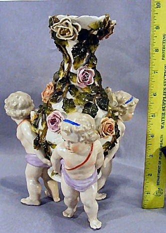 10D: German porcelain vase with 3 cupids along base, 9.