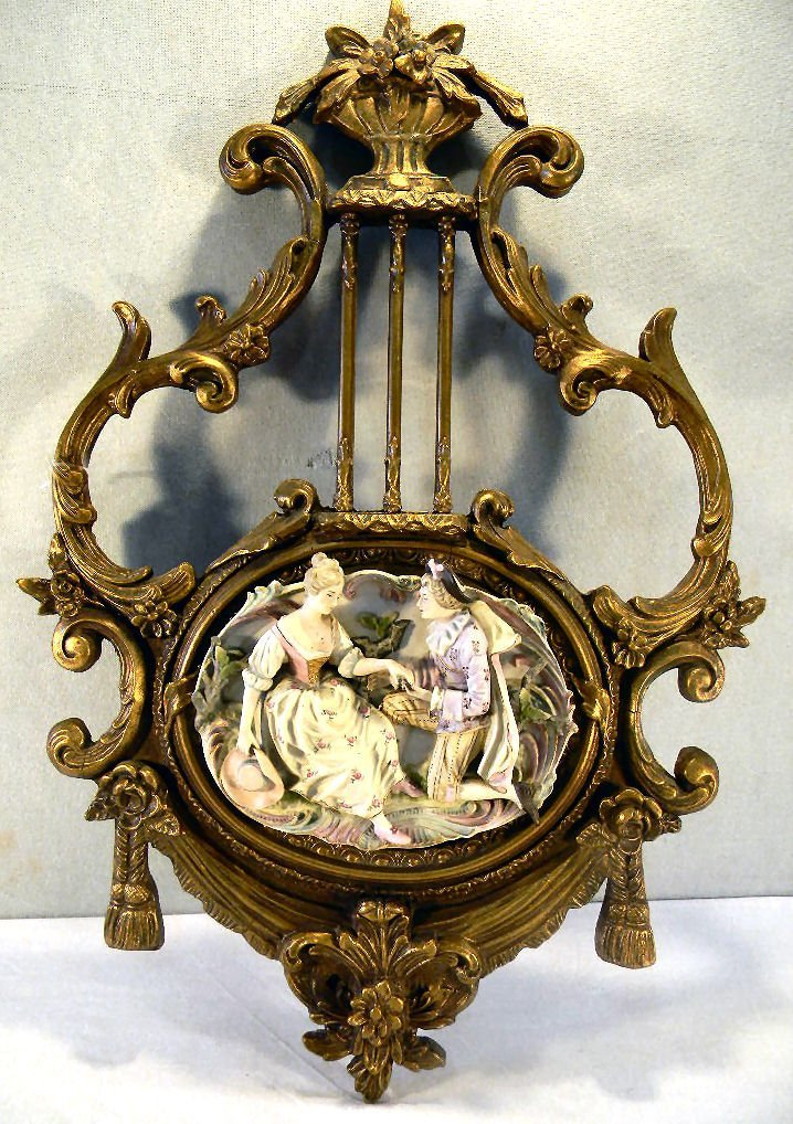 Oval bisque porcelain plaque mounted on ornate gilded f