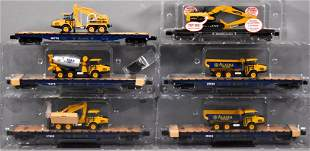 Six Menards O gauge flat cars with loads in five