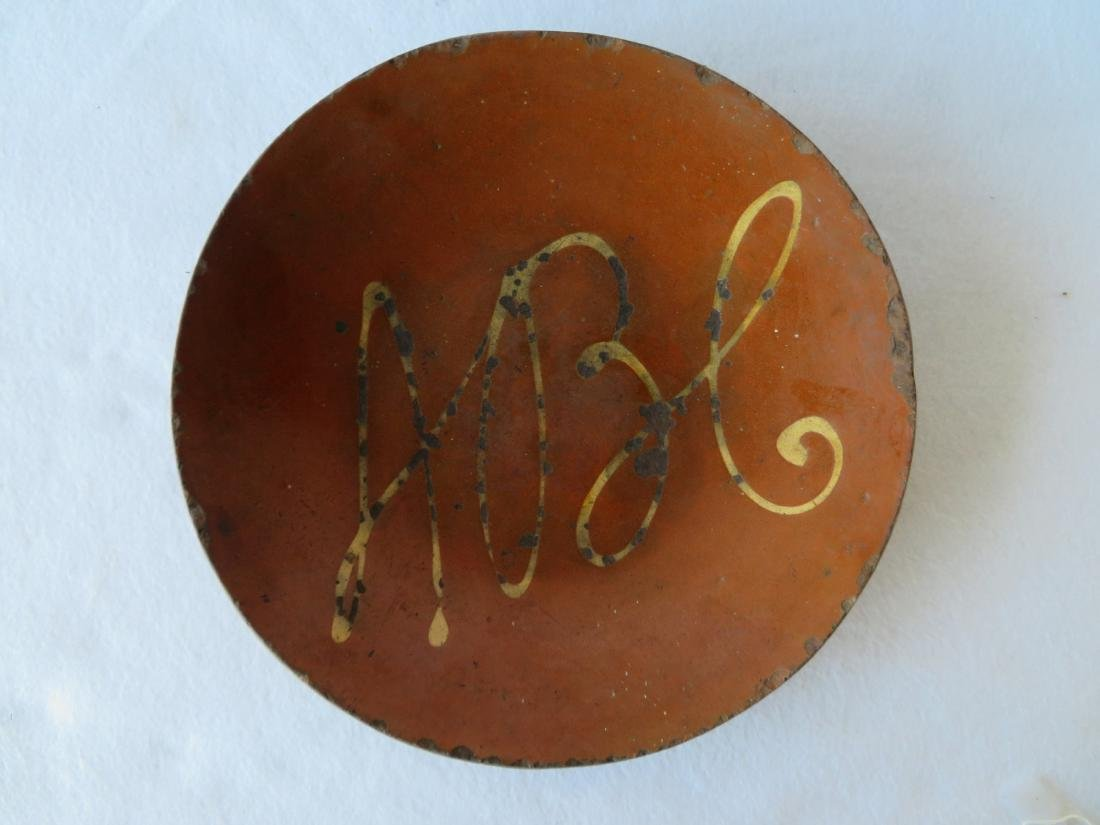 Redware charger decorated with a yellow slip ABC in the