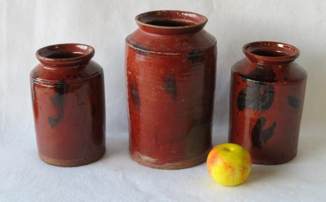 Three redware storage jars with manganese decorations