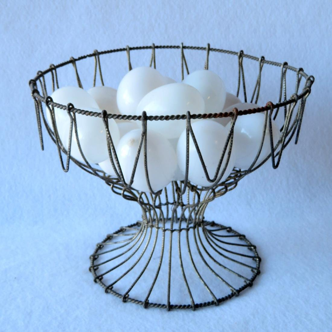 Wire egg basket holding 15 hand blown glass eggs, all