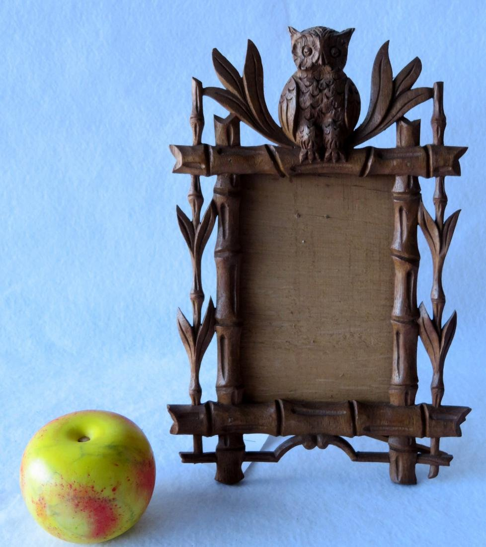 Rustic carved wooden frame with a seated owl finial,