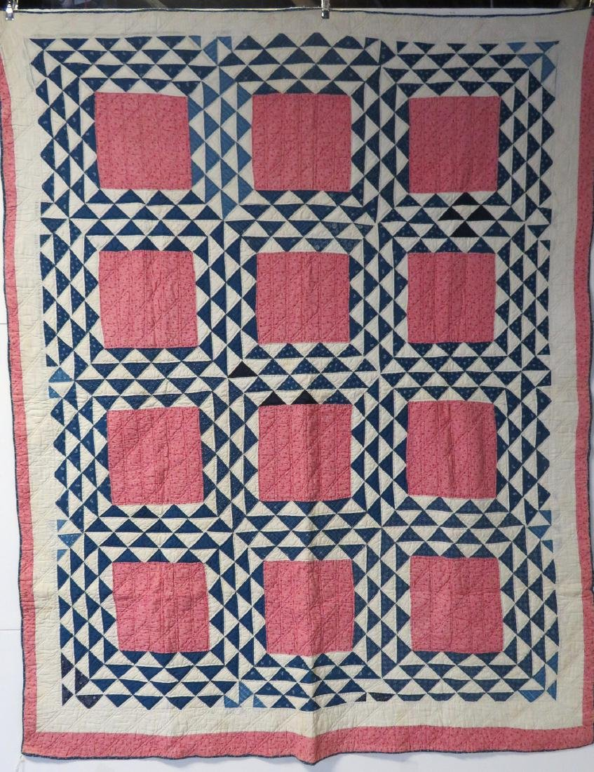 Patchwork quilt with blue flying geese surrounding pink