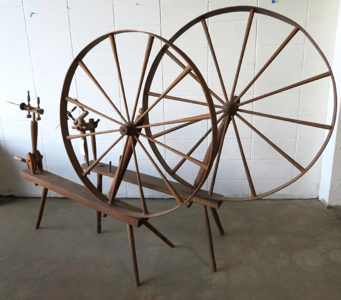 Two spinning great wheels with a small box of parts -