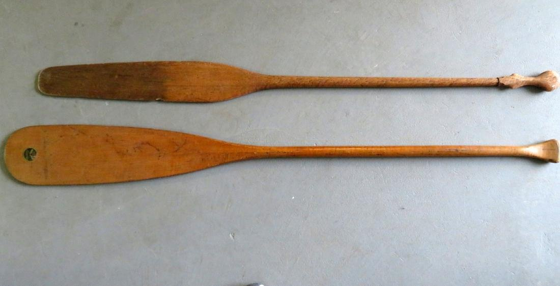 Two carved wooden canoe paddles: 1) Strong birdseye