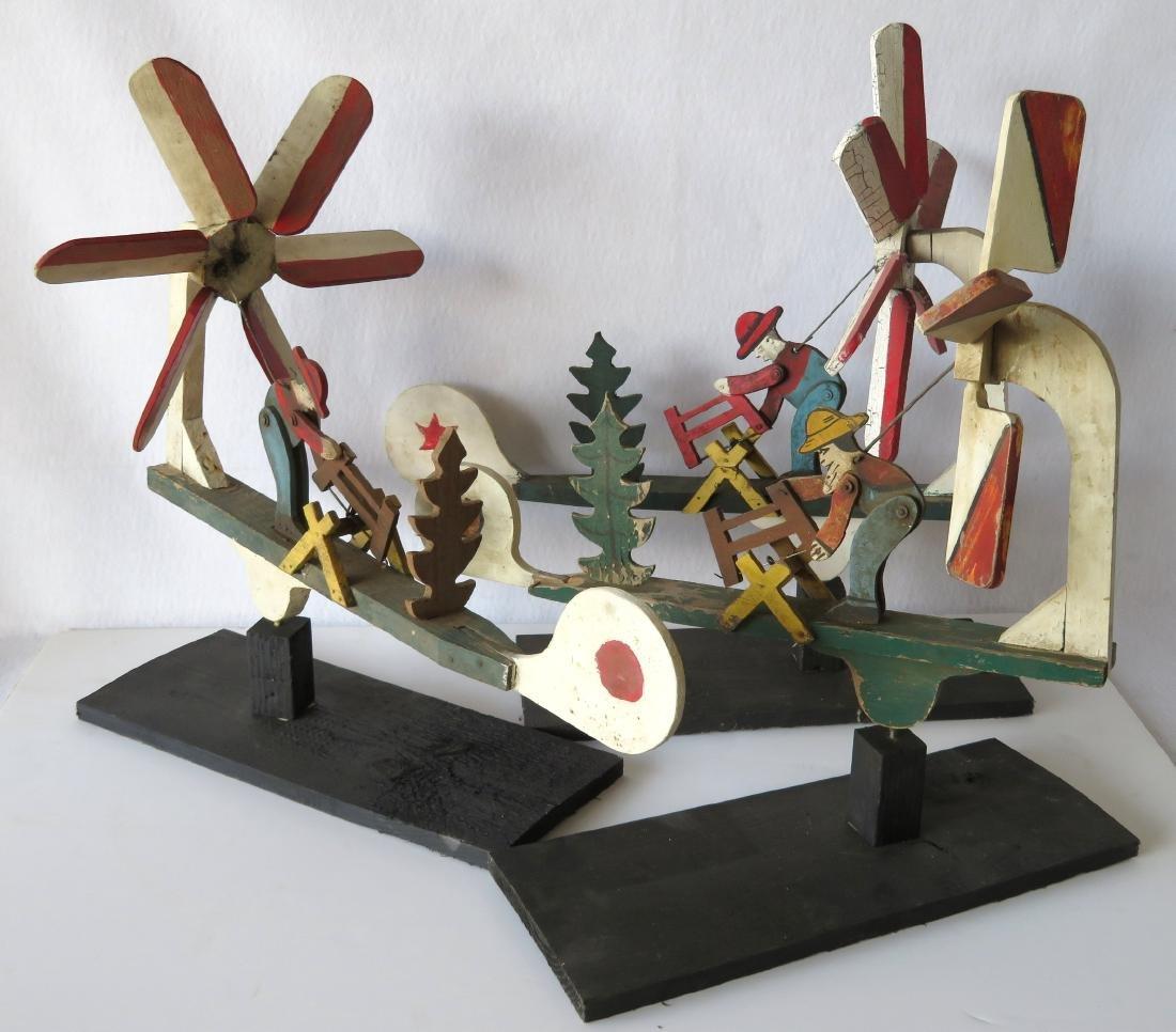 Three folk art whirligigs of man sawing log adjacent to