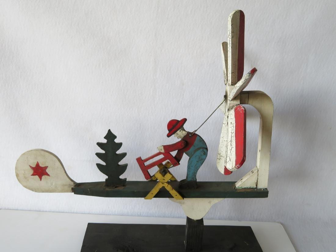 Three folk art whirligigs of man sawing log adjacent to - 2