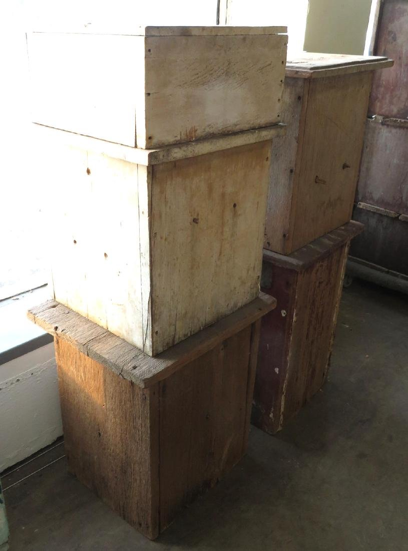 Four early wooden beehives in old paint, one in 2
