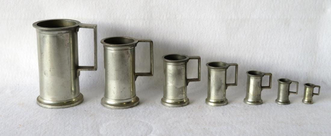 Set of 7 graduated pewter measures with touch mark GL